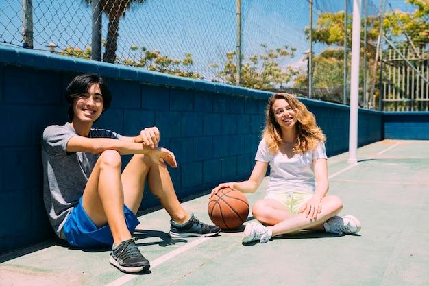 Feliz, adolescentes, sentando, em, basquetebol, arremesso Foto gratuita