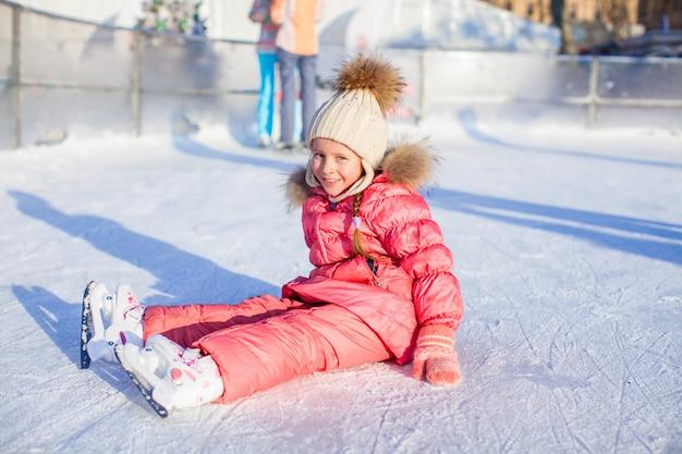 Feliz, adorável, menina, sentando, ligado, gelo, com, patins, após, a, outono Foto Premium