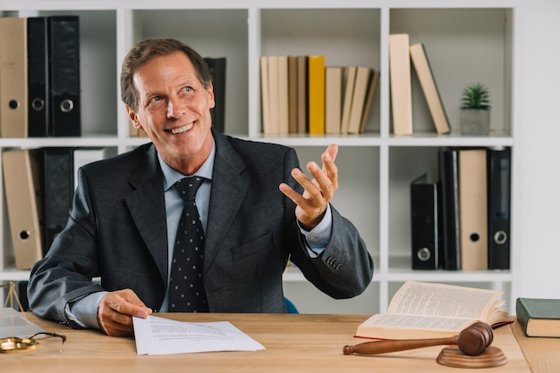 Feliz advogado maduro sentado na sala de tribunal gesticulando Foto gratuita