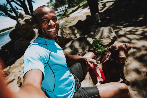 Feliz, africano, homem, com, cão, fazendo, selfie Foto Premium