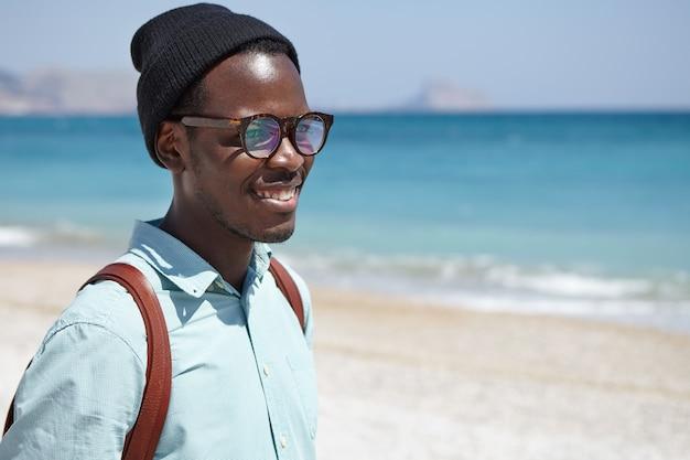 Feliz afro-americano jovem atraente vestido com roupas da moda e acessórios relaxantes à beira-mar, contemplando a paisagem azul no clima ensolarado e calmo, sentindo a conexão e harmonia com a natureza Foto gratuita