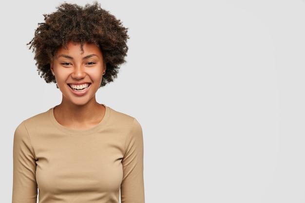Feliz alegre garota de pele escura sorrindo gentilmente Foto gratuita