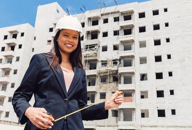 Feliz, americano africano, senhora, em, capacete segurança, com, medindo fita, perto, predios, construção Foto gratuita