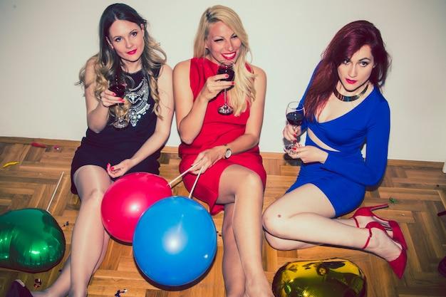 Feliz amigos posando com copos de vinho Foto gratuita