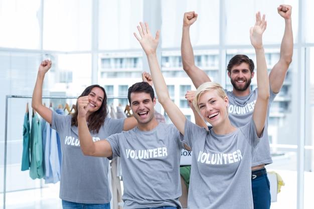 Feliz amigos voluntários, levantando os braços Foto Premium