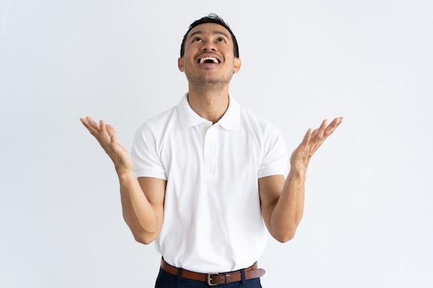 Feliz animado cara rezando para agradecer a deus Foto gratuita