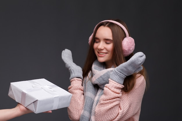Feliz animado jovem sorridente garota feliz no pulôver de tricô e protetores de orelha macios rosa com caixas de presente. Foto Premium