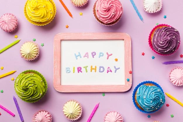Feliz aniversario de madeira na ardósia branca cercada com queques; aalaw; velas e granulado no fundo rosa Foto gratuita