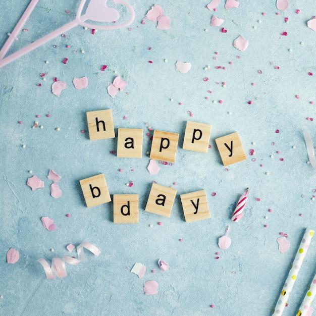 Feliz aniversário desejo em letras de madeira com velas e canudos Foto gratuita
