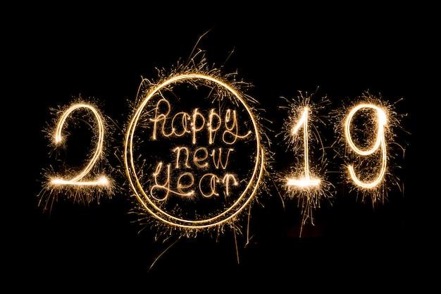 Feliz ano novo 2019 escrito com fogo de artifício de brilho Foto Premium