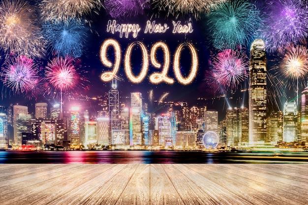 Feliz ano novo 2020 fogos de artifício sobre a paisagem urbana à noite com mesa de prancha de madeira vazia Foto Premium