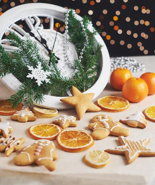 Feliz ano novo à meia-noite, velho relógio de madeira com luzes do feriado e ramos de abeto. cozinhar e decorar biscoitos de gengibre de natal e fatias de laranja fritas Foto Premium