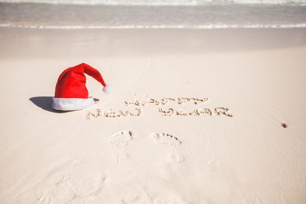 Feliz ano novo, escrito na areia e santa hat na praia de areia branca Foto Premium