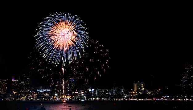 Feliz ano novo fogos de artifício sobre a paisagem urbana à noite. festival de celebração do feriado Foto Premium