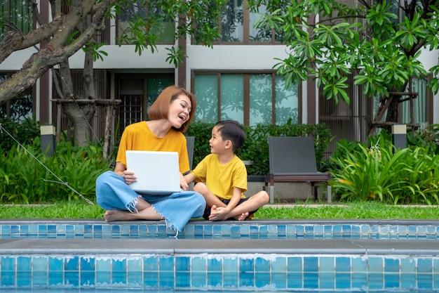 Feliz, asiático, mãe filho, usando computador portátil, em, ao ar livre, piscina Foto Premium