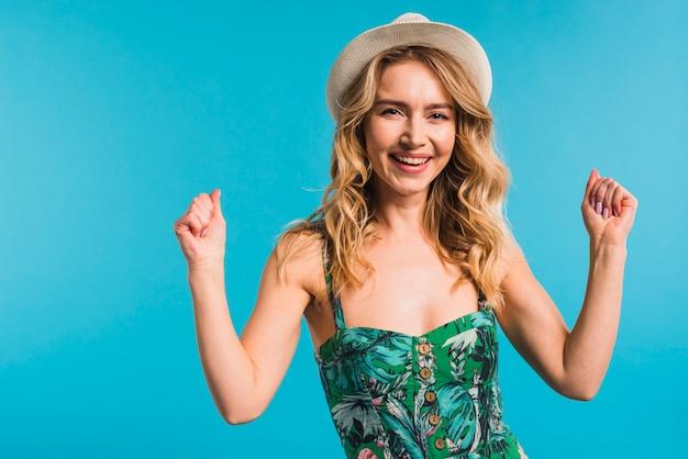 Feliz, atraente, mulher jovem, em, flowered, vestido, e, chapéu, mostrando, punhos Foto gratuita