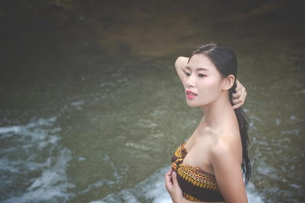 Feliz banho mulheres na cachoeira natural Foto gratuita