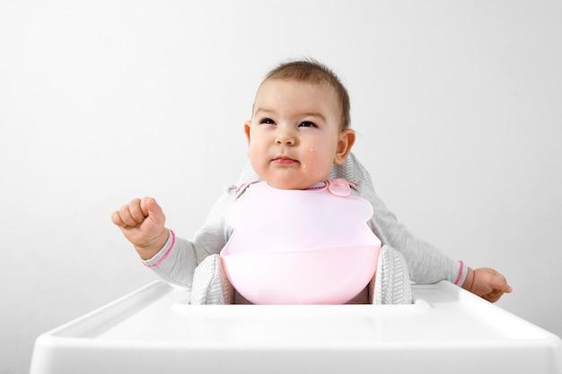 Feliz bebê criança na cadeira alta com colher na mão Foto Premium