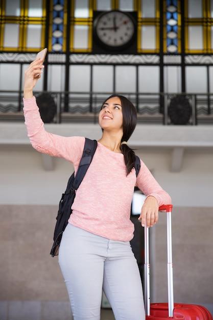 Feliz, bonito, mulher jovem, levando, selfie, foto, em, estação, corredor Foto gratuita
