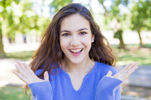 Feliz, bonito, mulher jovem, vomitando, mãos, parque Foto gratuita