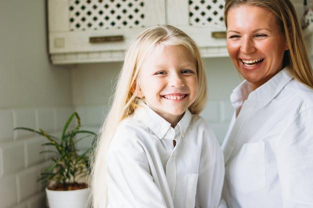 Feliz cabelos longos loiros mãe e filha se divertindo na cozinha, estilo de vida saudável e familiar Foto Premium