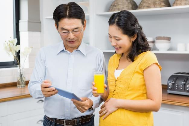 Feliz casal expectante usando tablet na cozinha Foto Premium