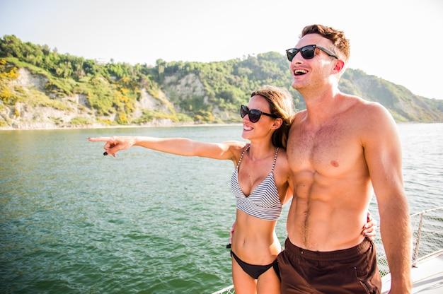 Feliz casal jovem apaixonado, abraçando no barco a vela flutuando no mar. jovens se divertindo no feriado, férias exclusivas Foto Premium