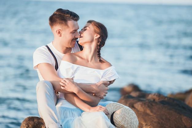 Feliz casal jovem romântico relaxante na praia e assistir o pôr do sol Foto gratuita