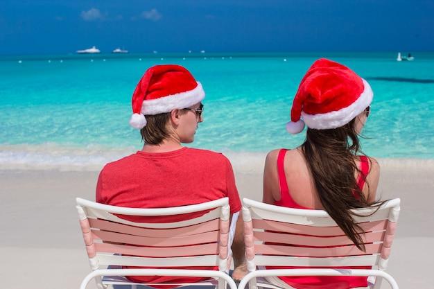 Feliz casal romântico em chapéus vermelhos de papai noel na praia tropical Foto Premium