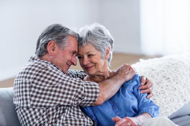 Feliz casal sênior, abraçando um ao outro no sofá Foto Premium