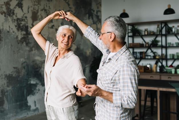 Feliz casal sênior dançando em casa Foto gratuita