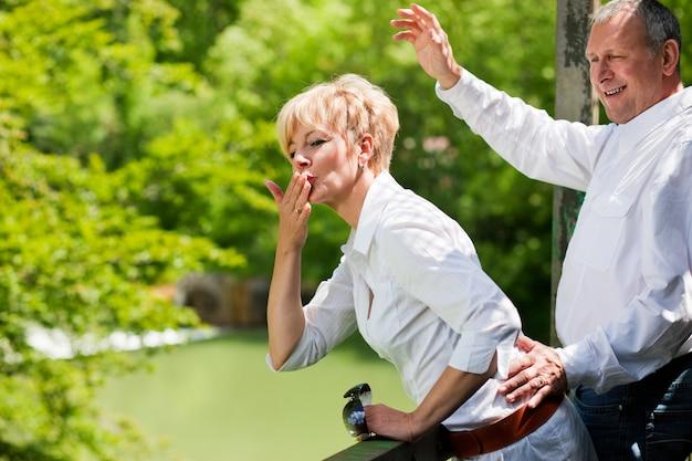 Feliz casal sênior na ponte acenando as mãos Foto Premium