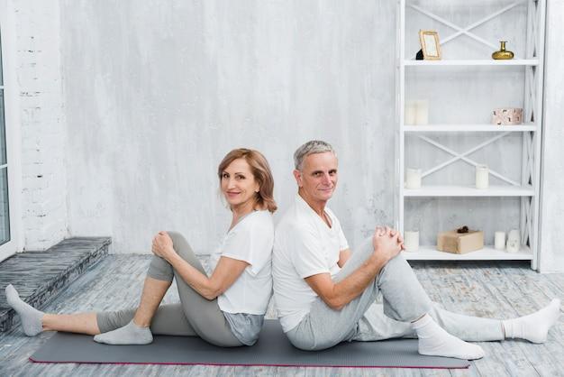 Feliz casal sênior sentado de costas no tapete de ioga cinza Foto gratuita