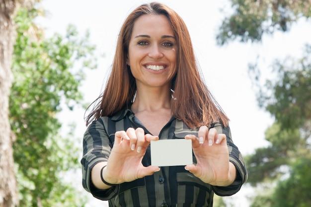 Feliz cliente feminino positivo segurando o distintivo branco Foto gratuita