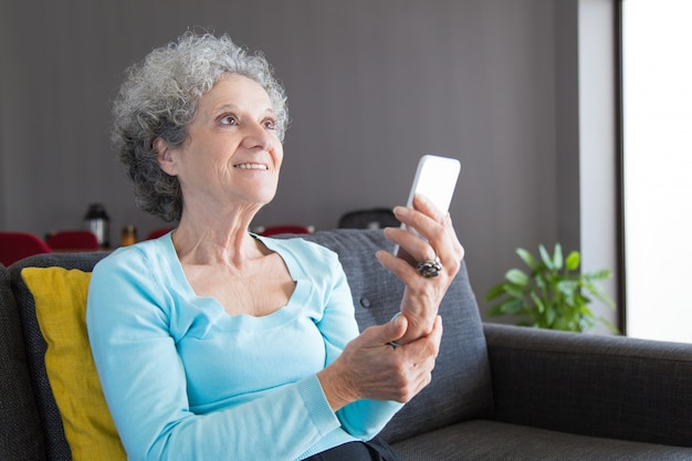 Feliz cliente sênior usando smartphone Foto gratuita