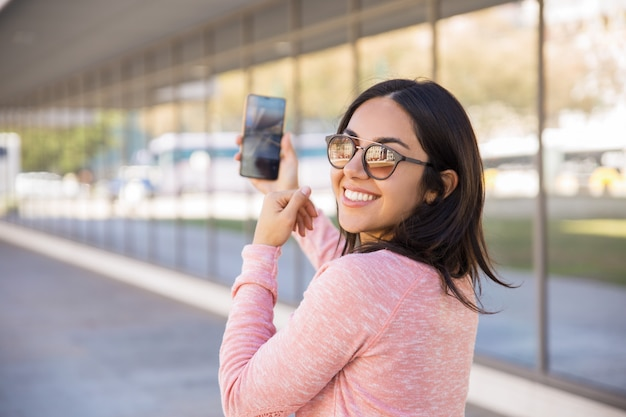 Feliz, consideravelmente, senhora jovem, levando, selfie, foto, ao ar livre Foto gratuita