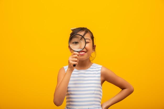 Feliz criança asiática com lupa Foto Premium