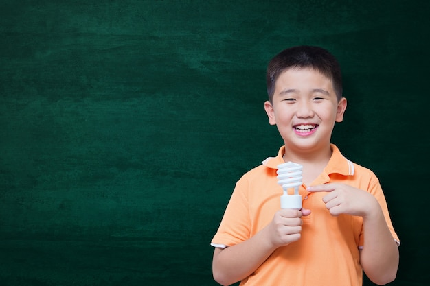 Feliz, criança asiática, sorrindo, ligado, vazio, verde, chalkboard Foto Premium