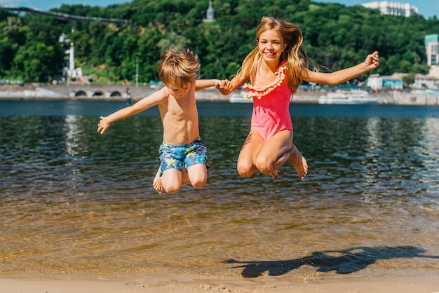 Feliz, crianças, pular, em, litoral Foto gratuita
