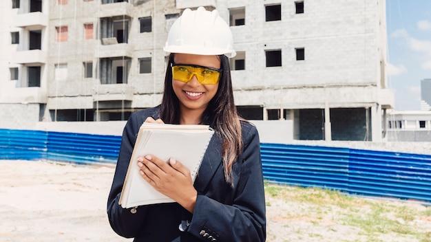 Feliz, dama americana africana, em, capacete segurança, escrita, em, caderno, perto, predios, construção Foto gratuita