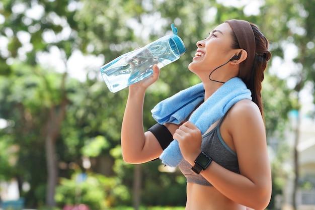 Feliz desportista água potável no parque Foto gratuita