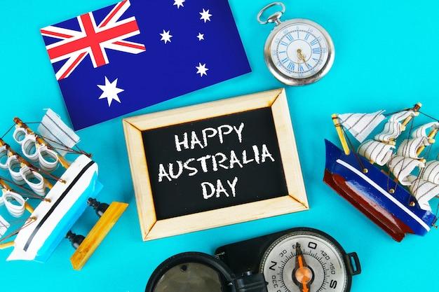 Feliz dia da austrália rodeado por shipwrights, uma bússola, relógio, bandeira australiana Foto Premium
