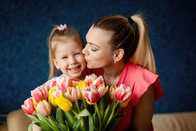 Feliz dia da mulher! a criança parabeniza a mãe e entrega flores tulipa. férias em família e união. Foto Premium
