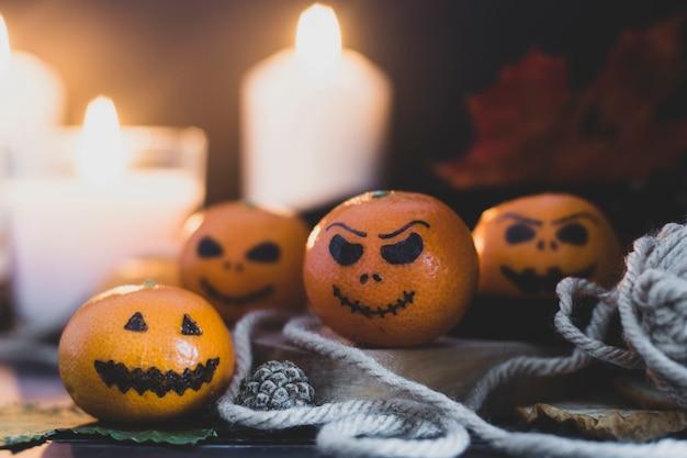 Feliz dia das bruxas cítrico, tangerinas pintadas com caras assustadoras e engraçadas. foto escura com velas. alternativas às abóboras tradicionais de halloween. Foto Premium