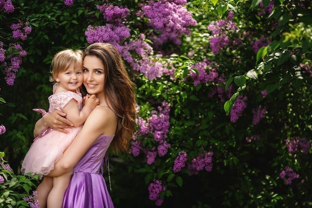 Feliz dia das mães! copie o espaço. mulher jovem e bonita e sua filha encantadora estão abraçando e sorrindo. árvores floridas Foto Premium