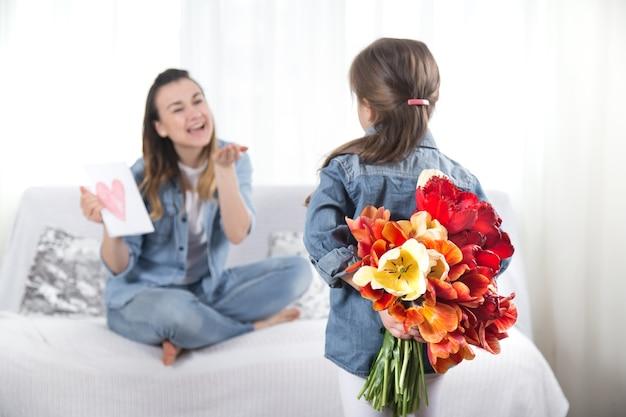 Feliz dia das mães. doce filha com um grande buquê de tulipas parabeniza sua mãe. no interior da sala, o conceito de uma vida familiar feliz Foto Premium