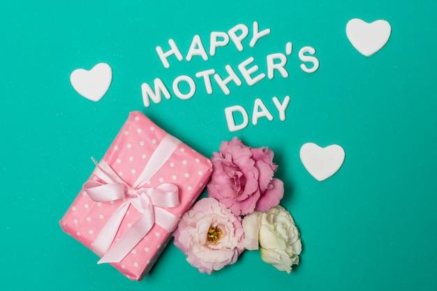 Feliz dia das mães título perto de flores e caixa de presente Foto gratuita