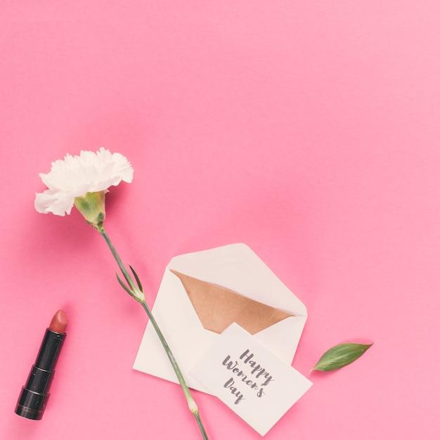 Feliz dia das mulheres inscrição com envelope e flor na mesa-de-rosa Foto gratuita