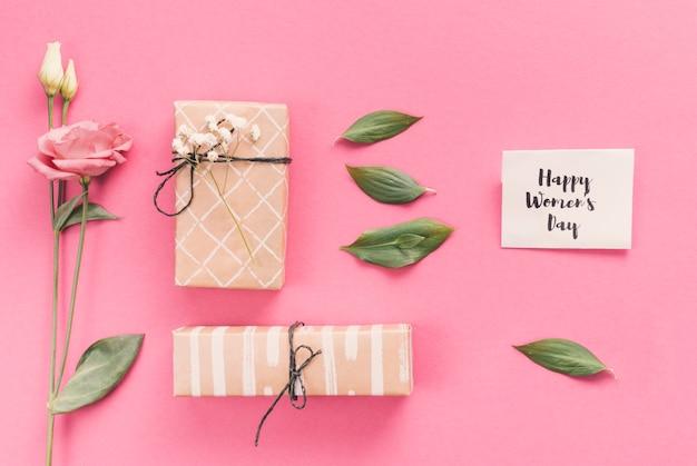 Feliz dia das mulheres inscrição com presentes e flores Foto gratuita