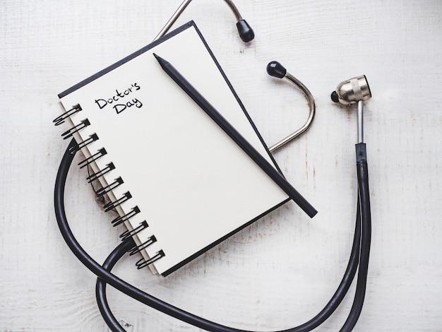 Feliz dia do médico. lindo cartão. caderno com inscrição de congratulações Foto Premium